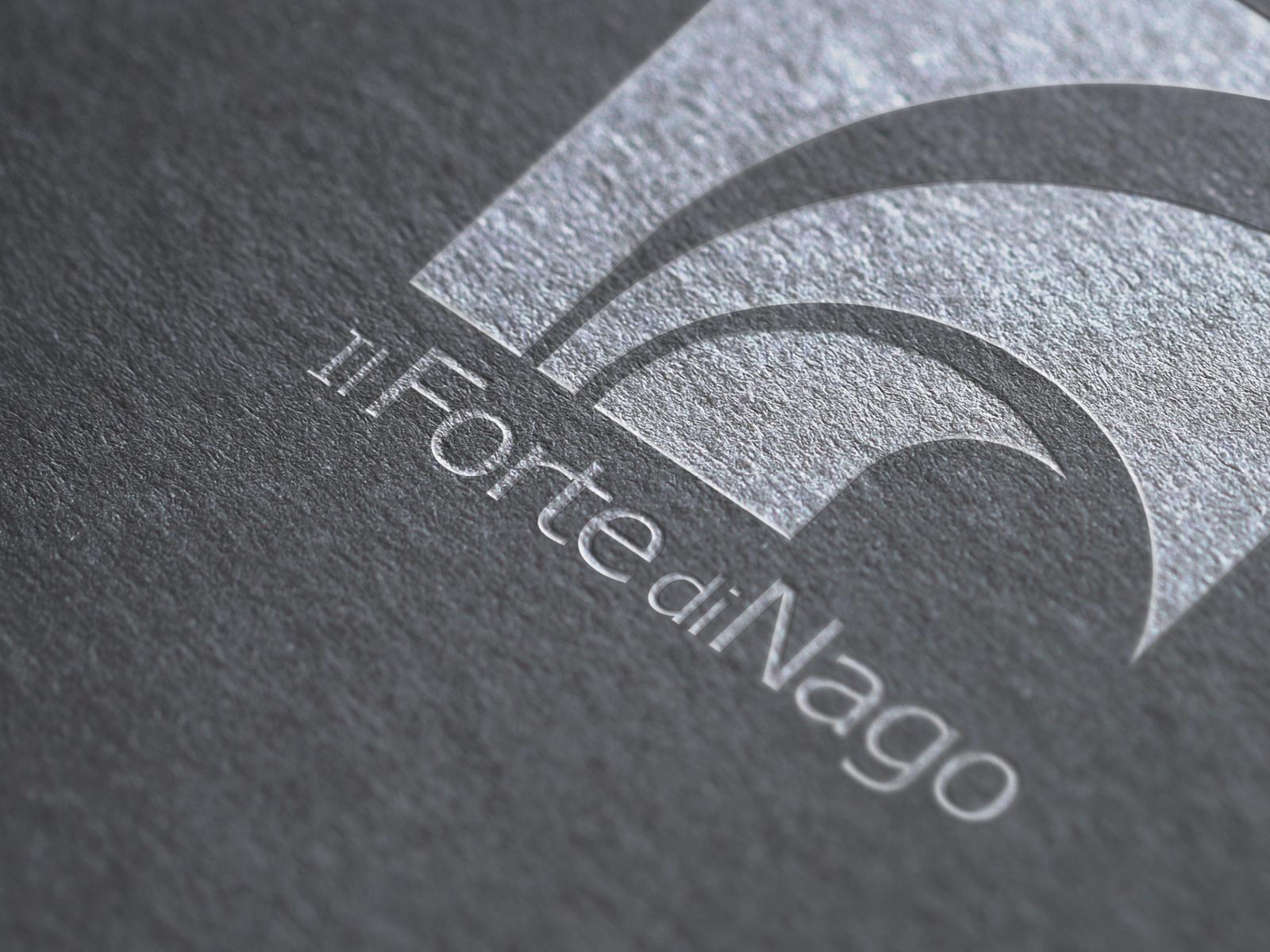 particolare del logo del forte di nago stampato su carta materica in colore bianco, progettato dalla agenzia diadestudio di arco trento